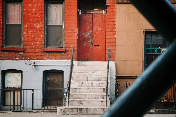 The entrance to a run-down red brick apartment building